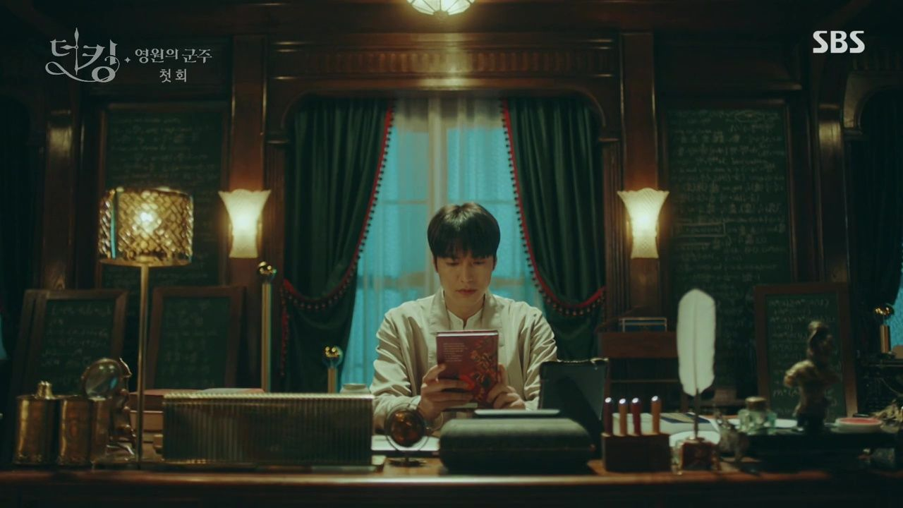 The King: Eternal Monarch King Lee Gon looking at white rabbit book and badge